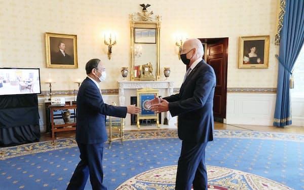日米豪印4カ国首脳会合を前にバイデン米大統領(右)の出迎えを受ける菅首相(24日、米ワシントンのホワイトハウス)=首相官邸のホームページより・共同