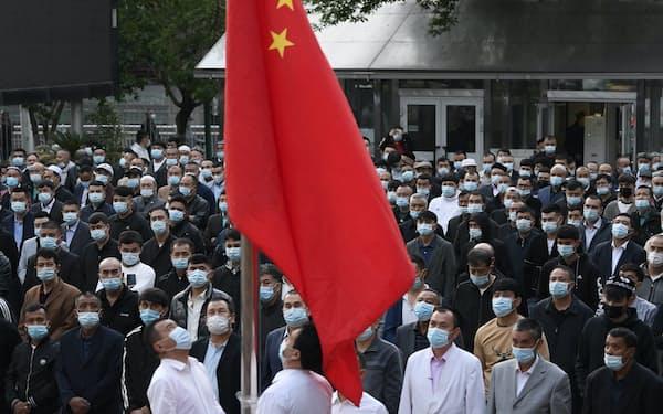 ヤンハンモスクで中国国旗の掲揚を見守るウイグル族住民ら(5月、新疆ウイグル自治区ウルムチ市)=共同