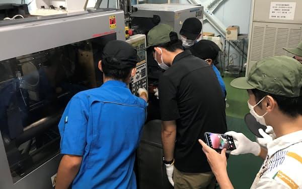 現場従業員が見学者に機械の操作方法などを説明する(9月、堺市の河辺商会が開いたプレイベント)