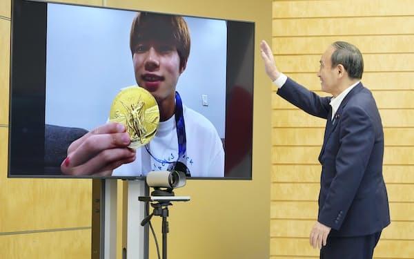 東京五輪スケートボード男子ストリートの金メダリスト、堀米雄斗選手とオンラインで面会した菅首相(27日午前、首相官邸)=共同