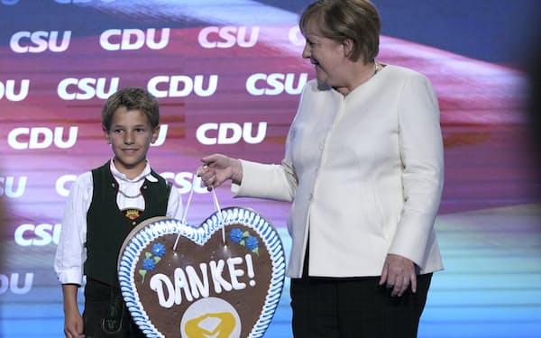 16年に及びドイツをけん引したメルケル首相は引退する(9月24日、「ありがとう」と書いた贈り物を渡す少年)=AP