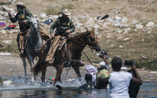 ハイチからの移民を馬に乗って取り締まる米国境警備隊員ら(19日、テキサス州デルリオ)=AP