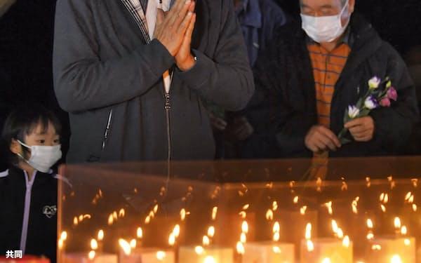 御嶽山の噴火から7年となり、追悼行事で手を合わせる遺族ら(27日夜、長野県木曽町)=共同