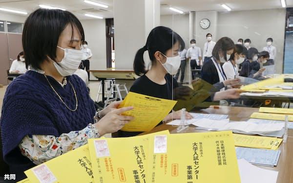 大学入学共通テストの出願受け付けが始まり、願書をチェックする関係者(27日、東京都目黒区)=共同