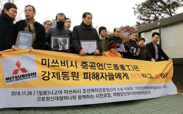 韓国最高裁の判決前に行進する元朝鮮女子勤労挺身(ていしん)隊訴訟の原告支援団体(2018年11月、ソウル)