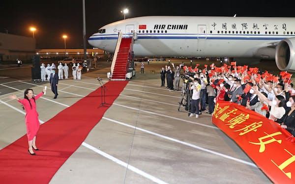 中国広東省深圳の空港に到着し、手を振るファーウェイの孟氏(左)=25日(新華社=共同)