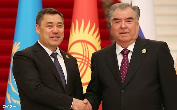 タジキスタンのラフモン大統領(右)と握手するキルギスのジャパロフ大統領(16日、ドゥシャンベ)=ロイター