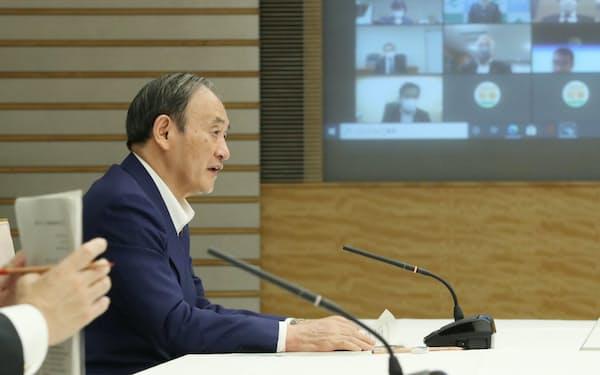 新型コロナ対策本部の会合で緊急事態宣言の全面解除を表明する菅首相(28日、首相官邸)
