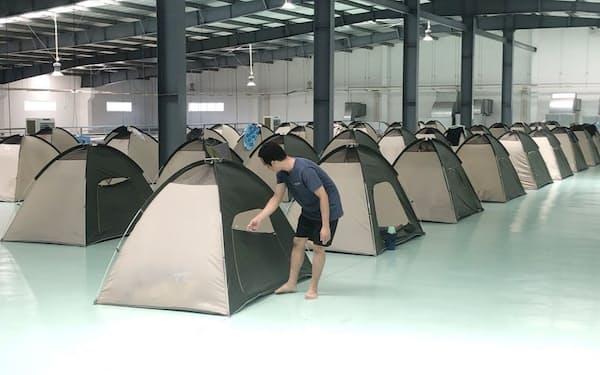 工場内に従業員が寝泊まりするためのテントを設置し、操業を続けている(ベトナム南部ドンナイ省)=国営ベトナム通信