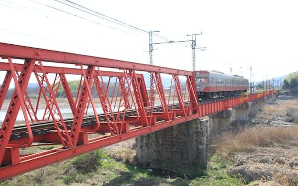 登録有形文化財の愛知川橋梁を渡る近江鉄道の電車