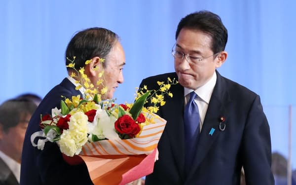 自民党の新総裁に選出された岸田文雄氏から花束を受け取る菅首相(29日、東京都港区)