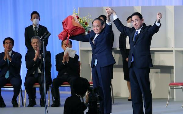 拍手に応える菅首相と自民党の岸田新総裁(29日、東京都港区)