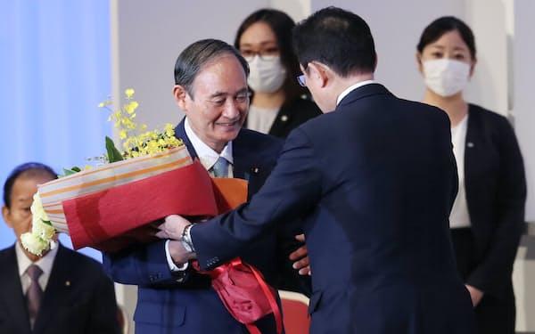 自民党の岸田新総裁から花束を受け取る菅首相(29日、東京都港区)