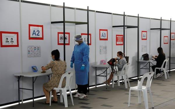 徹底した検査による早期発見がシンガポールの新型コロナウイルスの新規感染者数を押し上げている面もある(シンガポールのテストセンター)=ロイター