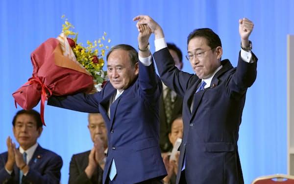 自民党総裁選を終え開かれた両院議員総会の壇上で、菅首相(左)と手を取り合う岸田新総裁=29日=共同