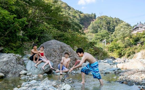 河原の野天風呂で湯あみを楽しむ地元客ら(長野県栄村)=三川 ゆき江撮影