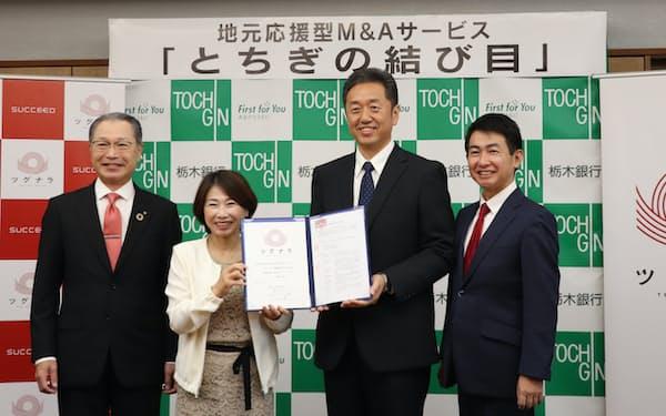 平成ハウジングの石槻博之社長(中央右)は「バウムハウス樹凜」を総美の郡司成江社長(中央左)に託した