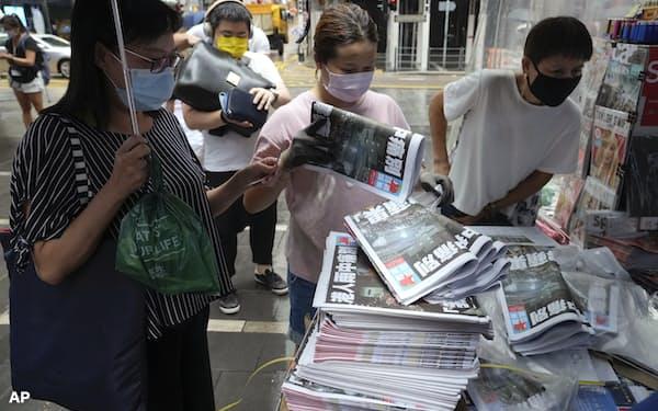 アップル・デイリーを買い求めようと殺到する人々(6月24日、香港)=AP