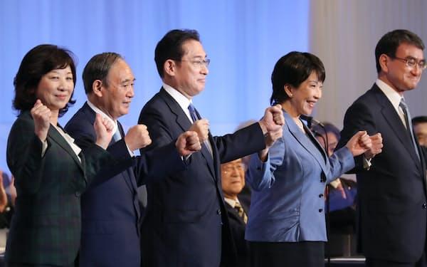 自民党の新総裁に選出され、菅首相や他の3候補と並んで拍手に応える岸田文雄氏(中央。9月29日、東京都港区)