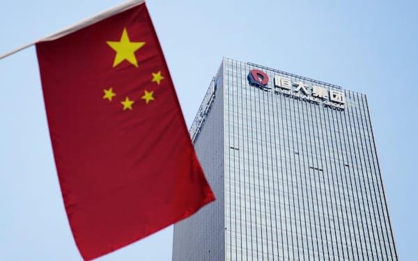 中国恒大集団の本社が入るビル。左はビル前の通りに掲げられた中国国旗(9月29日、中国広東省深圳市)=共同