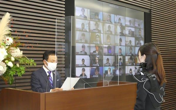 静岡銀行の八木副頭取(左)からウエアラブルカメラを装着した行員が内定通知書を受けとった(1日)