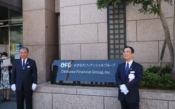 持ち株会社発足の式典で記念撮影に応じるおきなわFGの山城正保社長(右)
