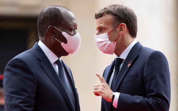 コートジボワールのワタラ大統領(左)と話すフランスのマクロン大統領(5月、パリの国際会議)=ロイター
