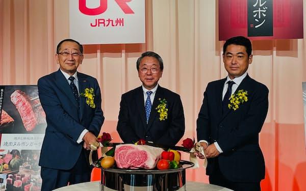 焼肉ヌルボンのJR九州傘下入りを記念し、肉に「入刀」する綱屋の萩原会長㊥ら(1日、福岡市)