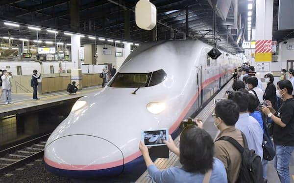 オール2階建て新幹線車両「E4系」をカメラに収める人たち(10月1日午後、JR新潟駅で)=共同
