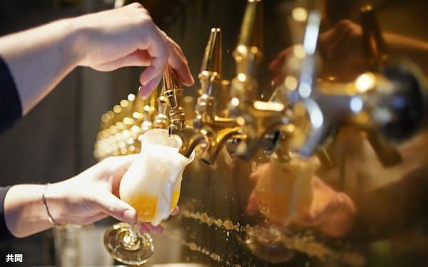 緊急事態宣言が解除された名古屋市内のバーで、グラスに注がれるビール(1日午後)=共同