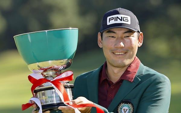 通算14アンダーで優勝し、カップを手に笑顔のチャン・キム(3日、三好CC)=共同