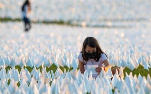 2021年9月、米国の首都ワシントンDC。連邦議会議事堂や様々な記念碑、博物館が集まる区域「ナショナルモール」の芝生で、新型コロナウイルス感染症による死者をしのぶ白い旗が、ボランティアの手によって立てられた。(PHOTOGRAPH BY STEPHEN WILKES)