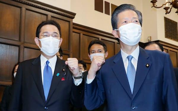 首相に選出され、公明党の山口代表(右)と拳を合わせる自民党の岸田総裁(4日、国会内)