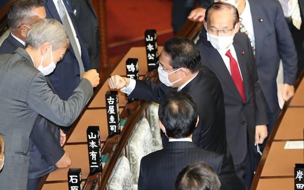 衆院本会議で首相に選出され、石原伸晃氏と拳を合わせる自民党の岸田文雄総裁(4日)