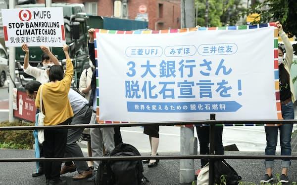 三菱UFJフィナンシャル・グループの株主総会会場前で環境対策を訴える人たち(6月29日、東京都港区)
