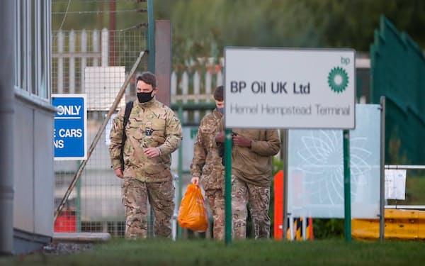石油貯蔵所の施設内を歩く軍人(4日、ロンドン北郊)=ロイター
