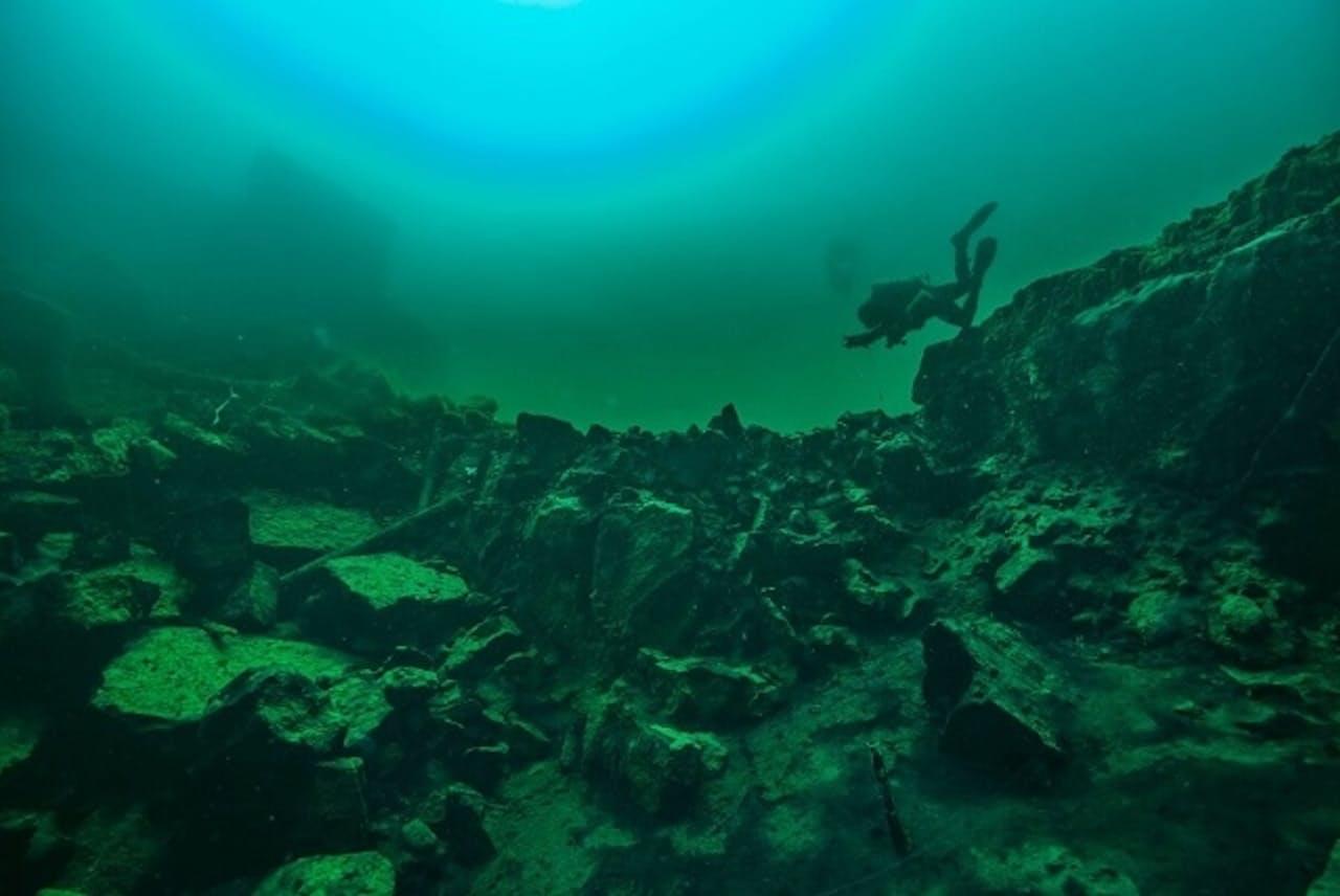 米五大湖のひとつヒューロン湖の陥没穴「ミドルアイランド・シンクホール」を探索するダイバー。ここの微生物マットは、約20億年前の地球の海のものと似ていると見られ、今回の研究に使われた(PHOTOGRAPH BY NOAA, THUNDER BAY NATIONAL MARINE SANCTUARY)