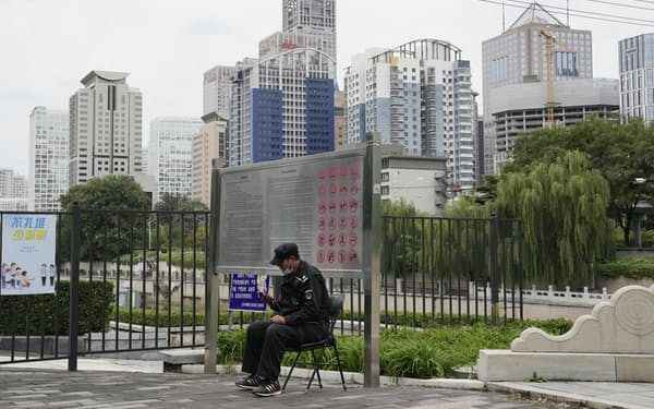 A security guard mans his post across from the central business district in Beijing, China, Tuesday, Oct. 5, 2021. Fantasia Holdings Group, a mid-size Chinese real estate developer, failed to make a $205.7 million payment due to bondholders Tuesday, adding to the industry's financial strain as one of China's biggest developers tries to avoid defaulting on billions of dollars of debt. (AP Photo/Ng Han Guan)