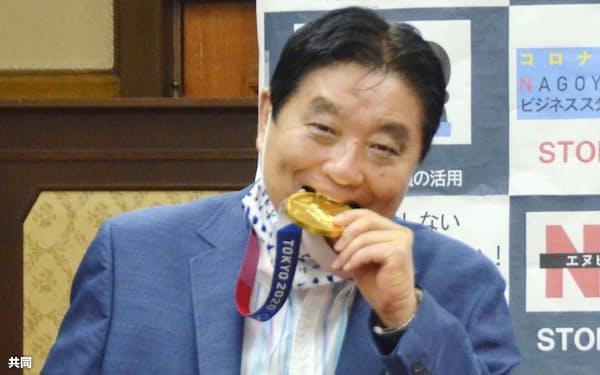 表敬訪問を受けた東京五輪日本代表選手の金メダルをかじる河村たかし名古屋市長(8月)=共同