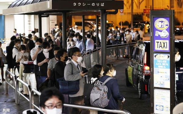 JR品川駅前で、タクシーを待ち列をなす大勢の人たち(8日午前0時49分)=共同