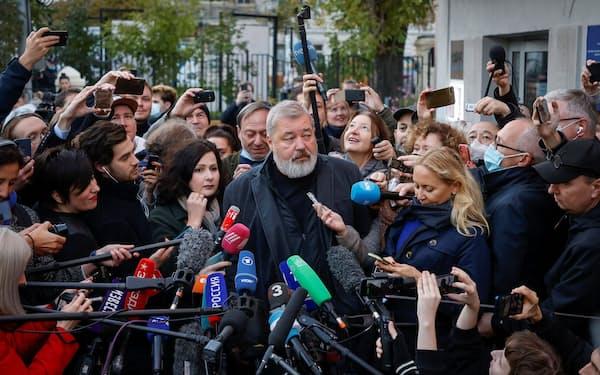 8日、モスクワ市内で記者会見したノーバヤ・ガゼータのムラトフ編集長(中央)=ロイター