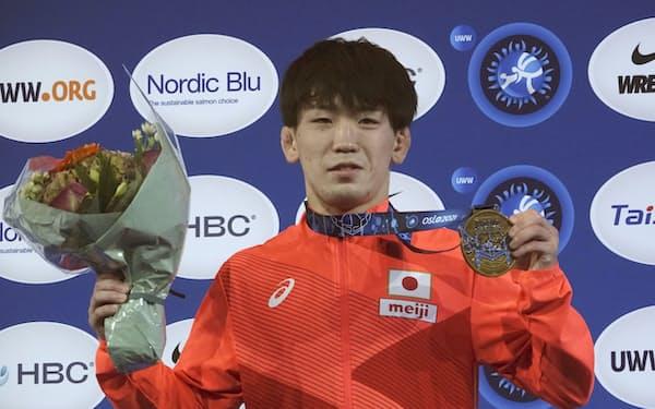 男子グレコローマンスタイル55キロ級で優勝し、金メダルを掲げる松井謙(8日、オスロ)=日本レスリング協会提供・共同