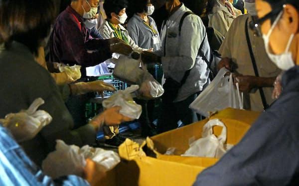 炊き出しに並ぶ人たち(9日、東京都豊島区の東池袋中央公園)