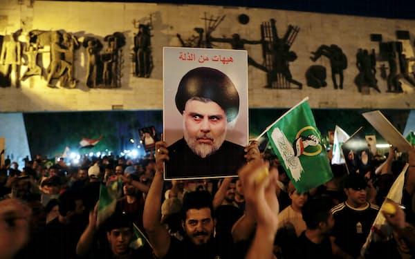 11日、サドル師の肖像を掲げ、議会選での勝利を祝う支持者ら(バグダッド)=AP