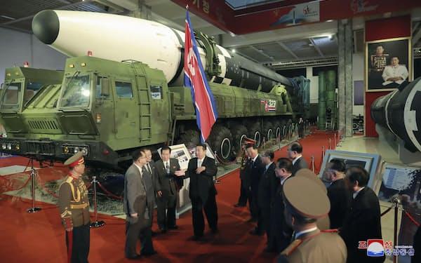 11日、兵器展覧会を視察する金正恩総書記(中央)=朝鮮中央通信・共同