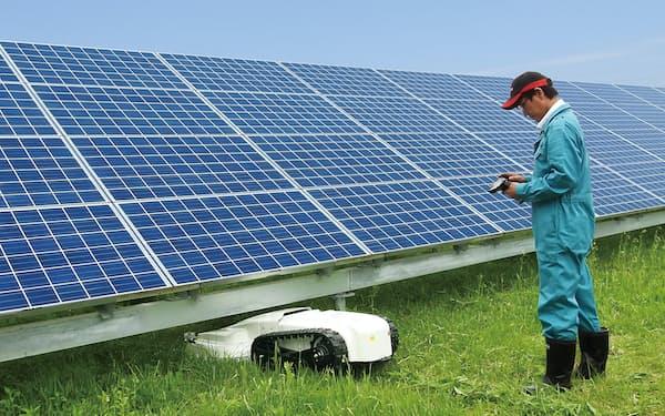 太陽光発電所の架台の下で草を刈るササキコーポレーションの電動リモコン作業機「スマモ」
