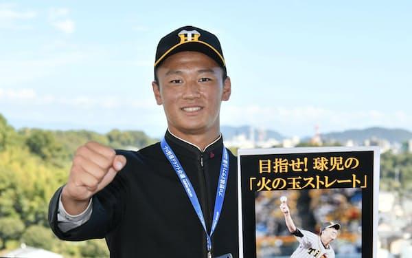 阪神からドラフト1位指名のあいさつを受け、藤川球児氏のパネルを手にポーズをとる高知高の森木大智投手(12日、高知市)=共同