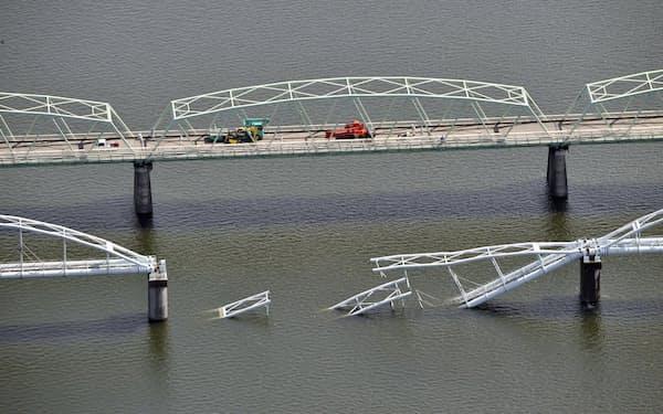 紀の川にかかる水道橋が崩落(手前)し、県道の橋(奥)では仮の水道管を設置する工事が進む=6日午前、和歌山市(共同通信社ヘリから)