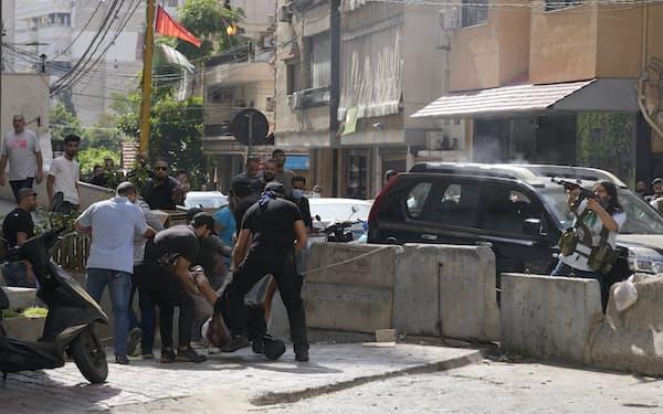 負傷者を救護するシーア派勢力ら(14日、ベイルート郊外)=AP