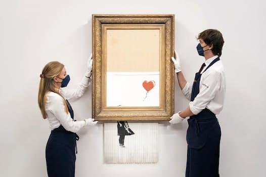 バンクシーの作品「愛はごみ箱の中に」を持つ展示担当者(9月3日、ロンドン)=AP